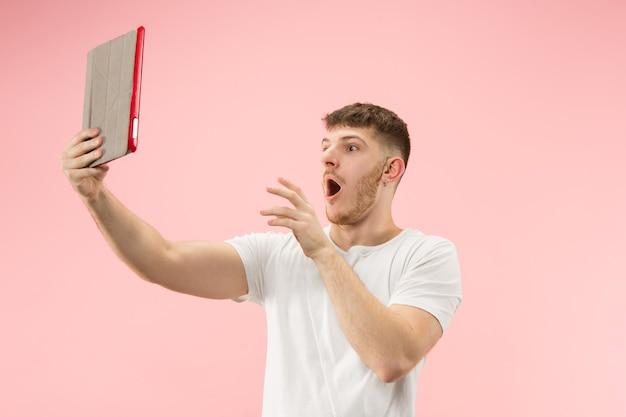Porträt des lächelnden mannes, der auf laptop mit leerem bildschirm lokalisiert auf rosa studio zeigt. Kostenlose Fotos
