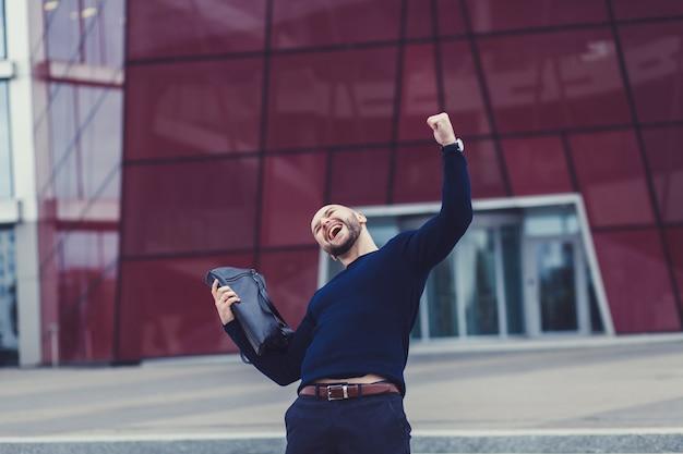 Porträt des lächelnden mannes mit den fäusten oben Premium Fotos