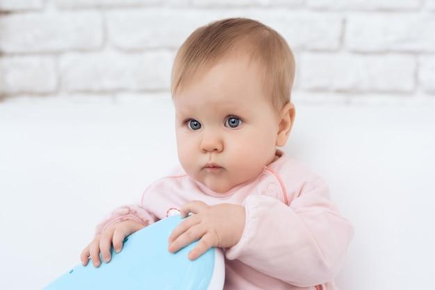 Porträt des lächelnden neugeborenen babys, das spielzeug spielt. Premium Fotos