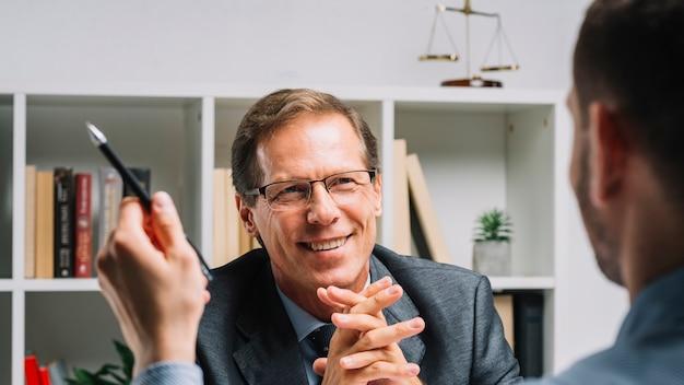 Porträt des lächelnden reifen rechtsanwalts, der mit geschäftskundenbehälter sitzt Kostenlose Fotos