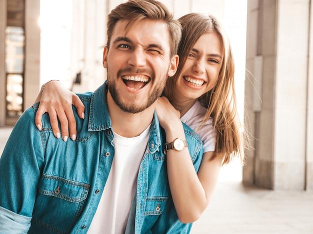 Porträt des lächelnden schönen mädchens und ihres hübschen freundes. frau in der beiläufigen sommerjeanskleidung. . zwinker Kostenlose Fotos