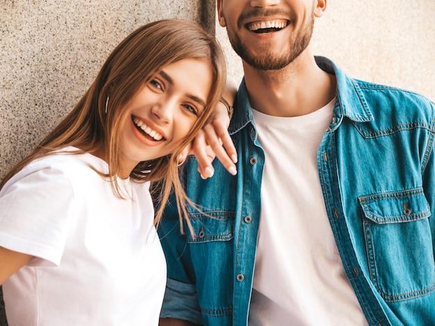 Porträt des lächelnden schönen mädchens und ihres hübschen freundes. frau in der beiläufigen sommerjeanskleidung. Kostenlose Fotos