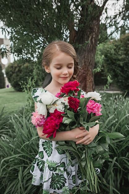Porträt des lächelnden schönen teenager-mädchens mit blumenstrauß von pfingstrosen gegen grünes gras am sommerpark. kindermode-konzept. Kostenlose Fotos