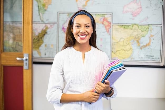 Porträt des lächelnden schullehrers bücher im klassenzimmer halten Premium Fotos
