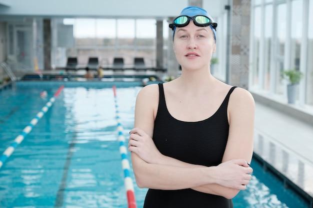 Porträt des lächelnden selbstbewussten jungen weiblichen schwimmers in schutzbrille und mütze, die mit verschränkten armen gegen schwimmbad stehen Premium Fotos
