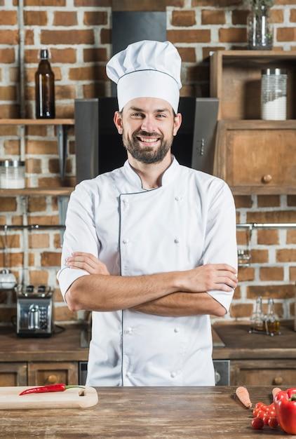 Porträt des lächelnden überzeugten männlichen chefs, der hinter dem küchenarbeitsplatte steht Kostenlose Fotos