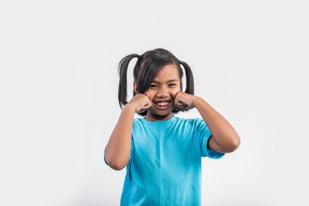 Porträt des lustigen kleinen mädchens, das in der atelieraufnahme fungiert Kostenlose Fotos