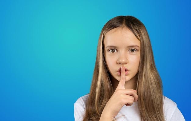 Porträt des mädchenkindes finger auf ihren lippen halten und bitten, ruhig zu bleiben Premium Fotos