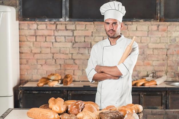 Porträt des männlichen bäckers das nudelholz halten, das hinter den gebackenen broten auf tabelle steht Kostenlose Fotos
