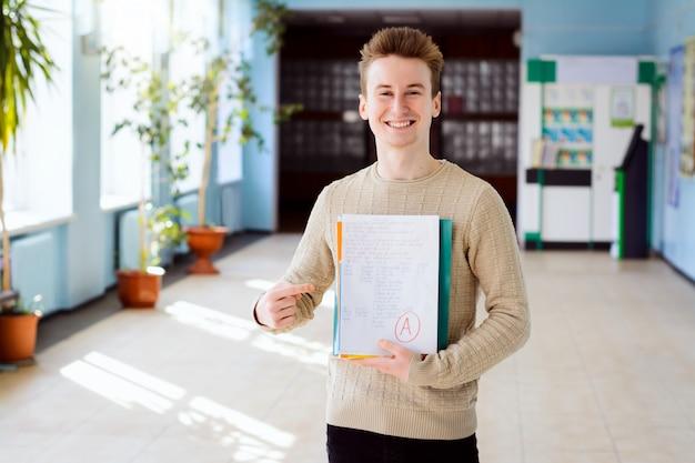 Porträt des männlichen studenten lächelnd an der kamera und auf die lernmaterialien zeigend Premium Fotos