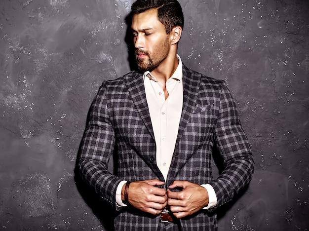 Porträt des männlichen vorbildlichen mannes der sexy hübschen mode kleidete im eleganten anzug an, der nahe grauer wand aufwirft Kostenlose Fotos