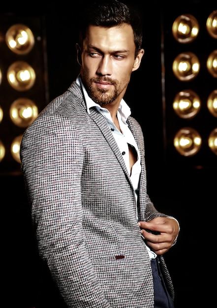 Porträt des männlichen vorbildlichen mannes der sexy hübschen mode kleidete im eleganten anzug auf schwarzem studio lichthintergrund an Kostenlose Fotos