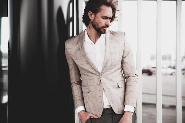 Porträt des männlichen vorbildlichen mannes der sexy hübschen mode kleidete im eleganten beige karierten anzug an, der auf dem straßenhintergrund aufwirft Kostenlose Fotos