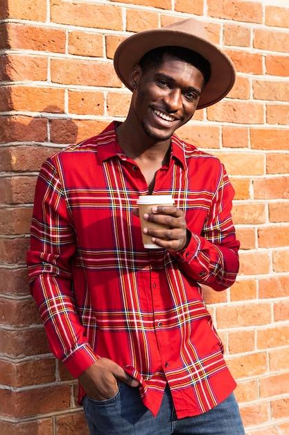 Porträt des mannes, der an eine wand lehnt und einen kaffee hält Kostenlose Fotos