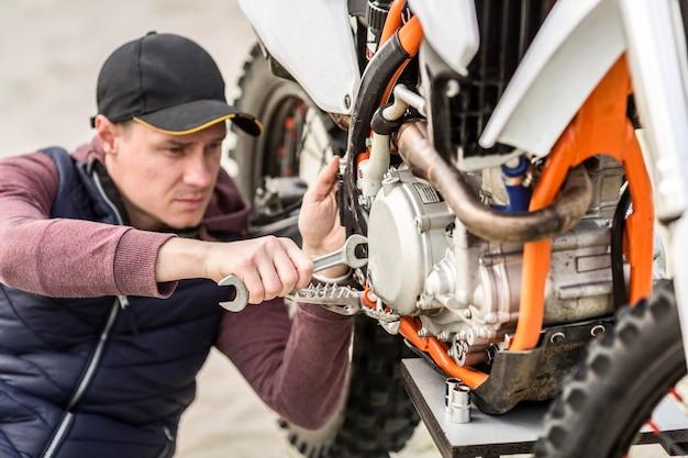 Porträt des mannes, der motorrad im freien repariert Kostenlose Fotos