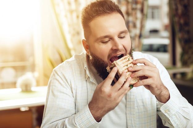 Porträt des mannes essend im café und lebensmittel genießend Premium Fotos