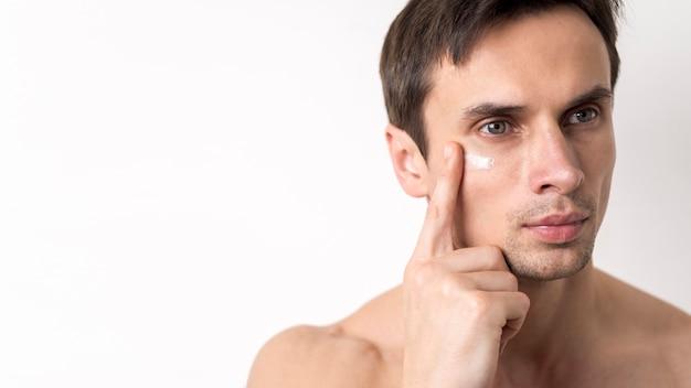 Porträt des mannes gesichtscreme auftragend Kostenlose Fotos