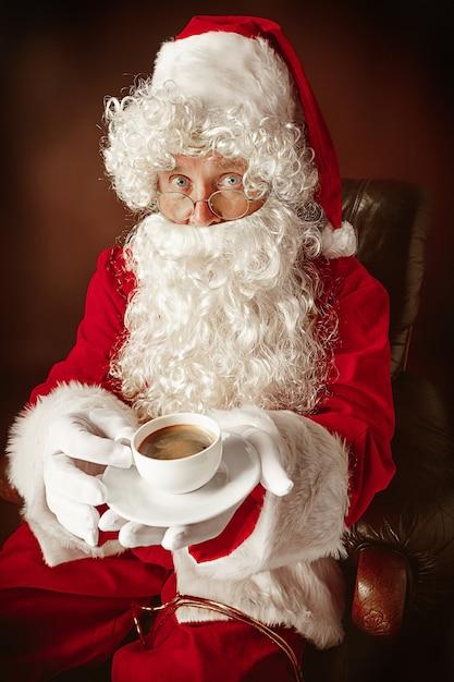 Porträt des mannes im weihnachtsmann-kostüm - mit einem luxuriösen weißen bart, der weihnachtsmann-mütze und einem roten kostüm am roten studiohintergrund, der in einem stuhl mit tasse kaffee sitzt Kostenlose Fotos