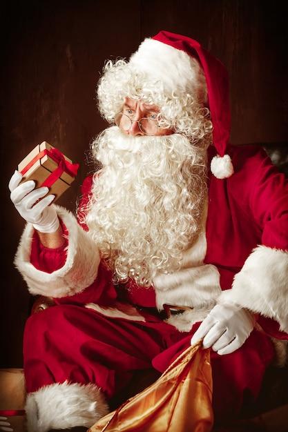 Porträt des mannes im weihnachtsmann-kostüm - mit einem luxuriösen weißen bart, der weihnachtsmann-mütze und einem roten kostüm im roten studio, das mit geschenken sitzt Kostenlose Fotos