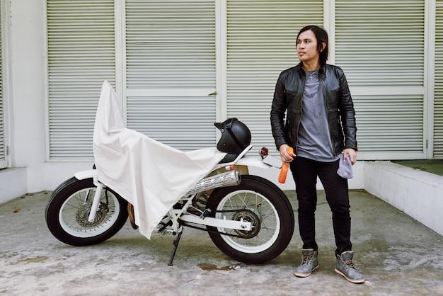 Porträt des mannes in der lederjacke, die mit dem poliermittel spreay an seinem fahrrad bedeckt durch überwurf steht Kostenlose Fotos