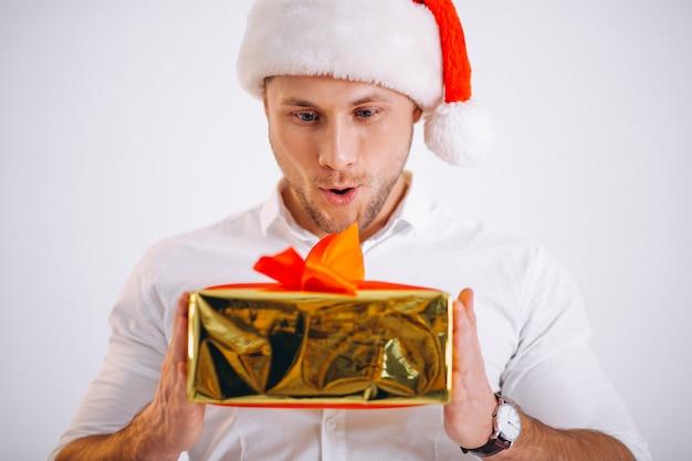 Porträt des mannes in sankt-hut, der weihnachtsgoldenen präsentkarton hält Kostenlose Fotos