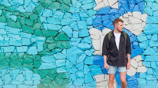 Porträt des mannes mit dem rucksack, der gegen gemalte steinwand steht Kostenlose Fotos