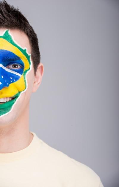 Porträt des mannes mit der brasilianischen flagge gemalt auf seinem gesicht. Premium Fotos