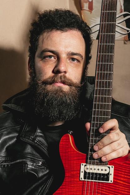 Porträt des mannes rote gitarre halten Kostenlose Fotos