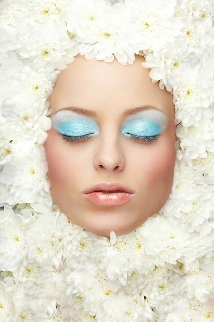 Porträt des modefrauenmodells mit hellem make-up liegt in den blumen Premium Fotos