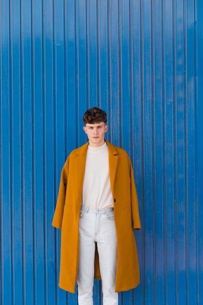 Porträt des modernen jungen gegen blaue wand Kostenlose Fotos