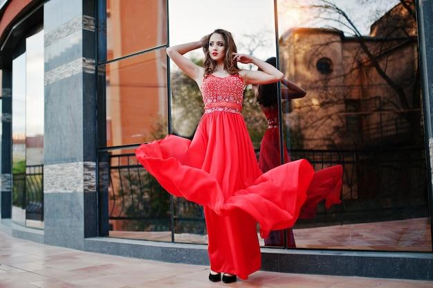 Porträt des modernen mädchens am roten abendkleid warf hintergrundspiegelfenster des modernen gebäudes auf. kleid in die luft blasen Premium Fotos