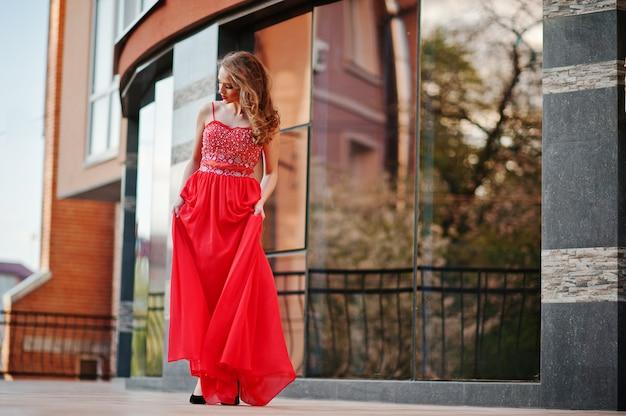 Porträt des modernen mädchens am roten abendkleid warf hintergrundspiegelfenster des modernen gebäudes auf Premium Fotos