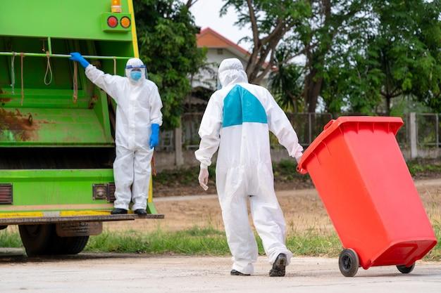 Porträt des müllsammlers in schutzkleidung psa-schutzkleidung tragen medizinischen gummi mit lkw-ladeabfällen und mülleimer, coronavirus-krankheit 2019, coronavirus hat sich zu einem globalen notfall entwickelt. Premium Fotos