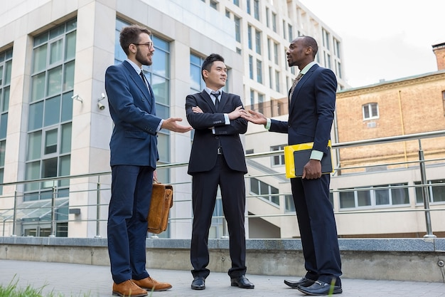 Porträt des multiethnischen geschäftsteams. drei lächelnde männer, die gegen den hintergrund der stadt stehen. der eine mann ist europäer, der andere ist chinese und afroamerikaner. Kostenlose Fotos