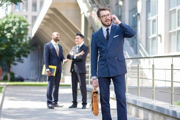 Porträt des multiethnischen geschäftsteams. drei männer, die vor dem hintergrund der stadt stehen. der vordergrund eines europäischen mannes, der am telefon spricht. andere männer sind chinesen und afroamerikaner. Kostenlose Fotos