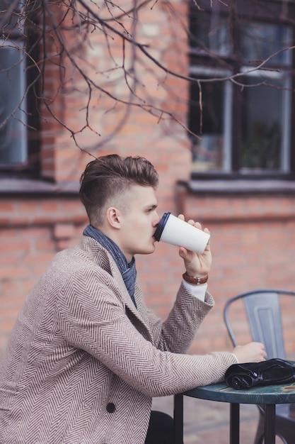 Porträt des nachdenklichen jungen geschäftsmannes, der kaffee vom pappbecher trinkt Premium Fotos