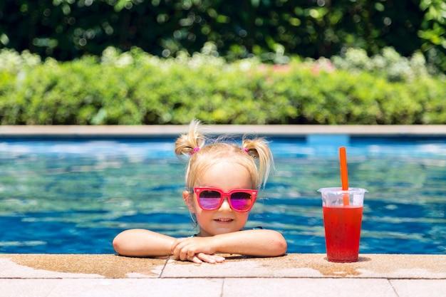 Porträt des netten glücklichen kleinen mädchens, das spaß im swimmingpool hat Premium Fotos