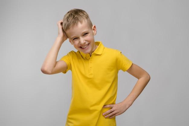 Porträt des netten kleinen blonden kaukasischen jungen im gelben t-shirt denkend auf grau Premium Fotos