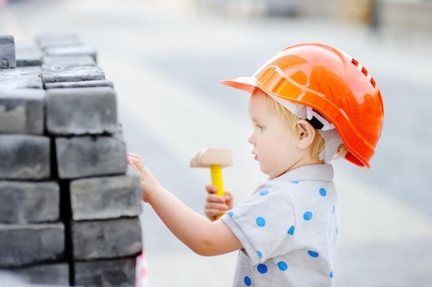 Porträt des netten kleinen erbauers in den hardhats mit dem hammer, der draußen arbeitet Premium Fotos