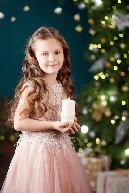 Porträt des netten langhaarigen kleinen mädchens im kleid an von lichtern. kleines mädchen, das brennende kerze hält. weihnachten, neujahr. Premium Fotos
