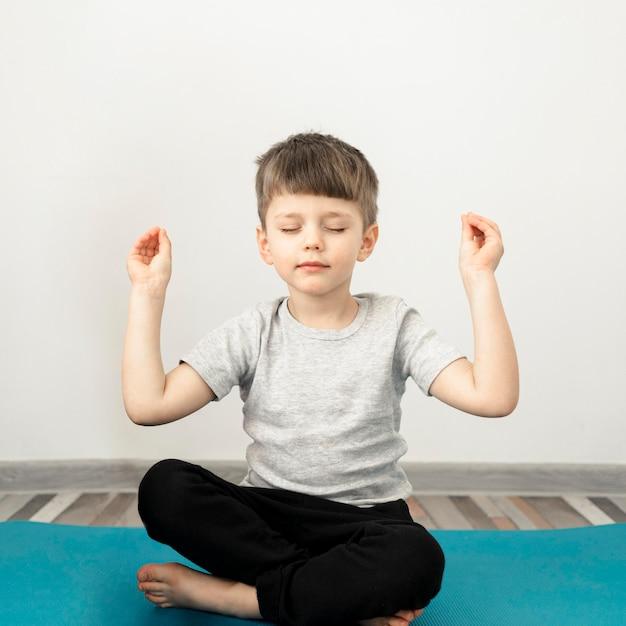 Porträt des niedlichen jungen, der yoga praktiziert Premium Fotos