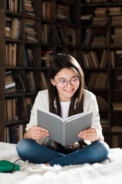 Porträt des niedlichen jungen mädchens, das ein buch liest Kostenlose Fotos