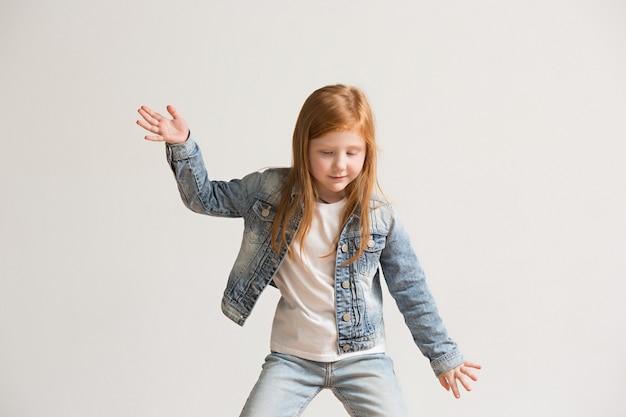 Porträt des niedlichen kleinen kindes in der stilvollen jeanskleidung, die kamera betrachtet und lächelt Kostenlose Fotos