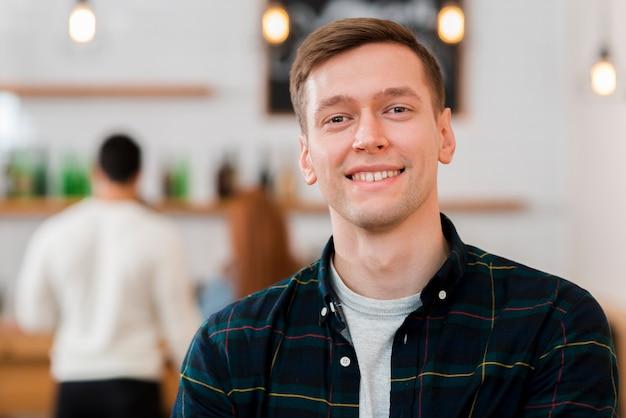 Porträt des niedlichen lächelnden jungen im café Kostenlose Fotos