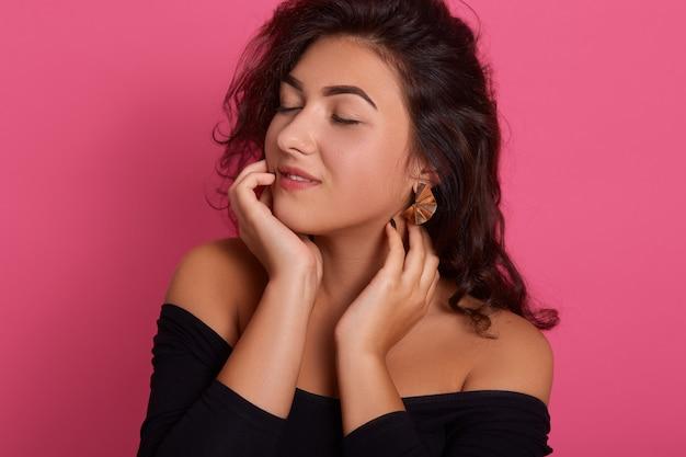 Porträt des niedlichen reizenden mädchens, das schwarzes outfit mit dunklem welligem haar trägt und mit geschlossenen augen auf rosa wand, attraktive dame voller träume aufwirft. Kostenlose Fotos