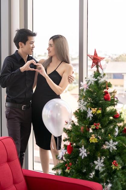 Porträt des paares, das neujahrs- und weihnachtsfestfeiertag im wohnzimmer der großen modernen wohnung feiert Premium Fotos