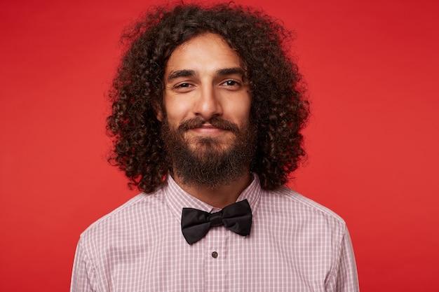 Porträt des positiven attraktiven brünetten lockigen kerls mit bart, der kariertes hemd und schwarze fliege trägt, während er aufwirft und mit sanftem lächeln schaut Kostenlose Fotos