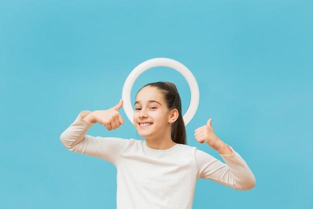 Porträt des positiven jungen mädchens, das daumen hoch zeigt Kostenlose Fotos