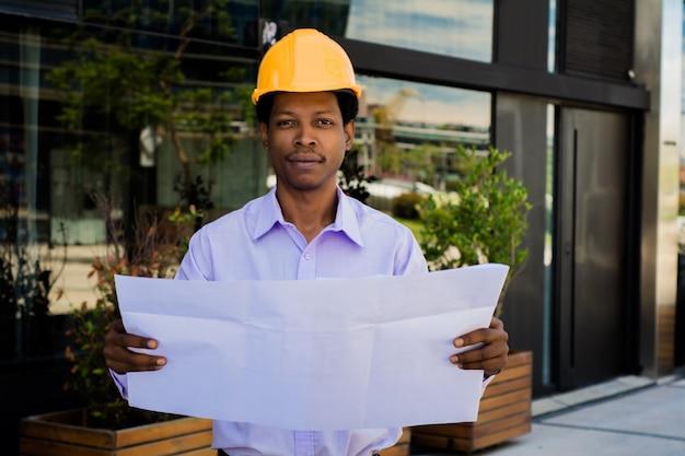 Porträt des professionellen architekten im helm, der blaupausen außerhalb des modernen gebäudes betrachtet. ingenieur- und architektenkonzept. Kostenlose Fotos