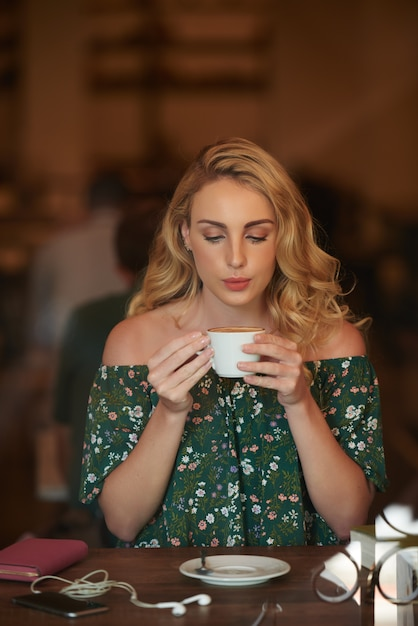 Porträt des recht blonden sitzens am cafétisch und des nippenden kaffees Kostenlose Fotos